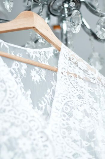 wedding peignoir on a hanger hanging on a chandelier opposite the window