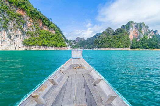 Wooden Thai traditional long-tail boat on a lake with mountains at Ratchaprapha Dam or Khao Sok National Park, Thailand