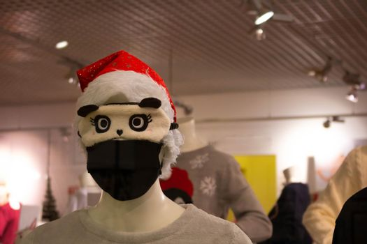 A mannequin in a Santa Claus hat wearing a black protective mask and a cute sleep mask.