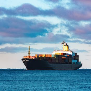 Modern black container ship moving from Baltic sea