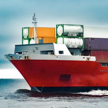 Red cargo container ship's bow in cloudy day