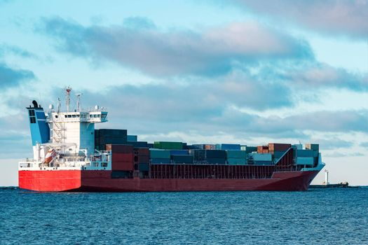 Full red container ship moving in still water