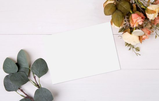 Valentine day, greeting card mockup and flower on wooden table, postcard blank and letter with romance on desk, present and paper in anniversary and celebration, top view, nobody, holiday concept.