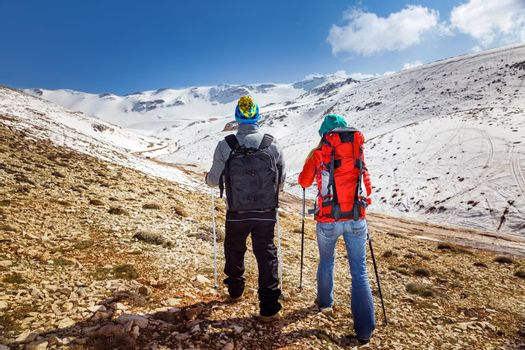 Back Side of a Young Family Hiking in the Mountains with Trekking Poles. Enjoying Amazing View on Beautiful Snowy Mountains. Happy Active Winter Holidays.