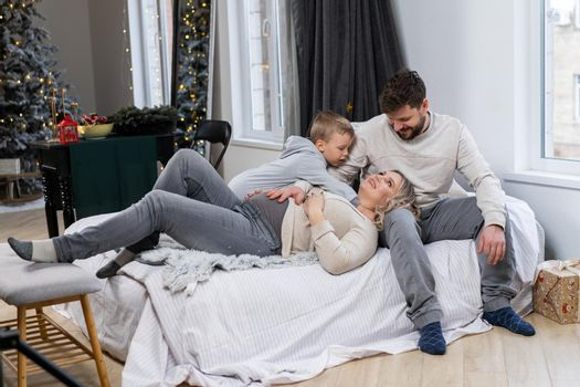 Happy family concept Mother father and little son have fun at home Caucasian family indoors Pregnant mom beard dad and funny little boy lie on the couch