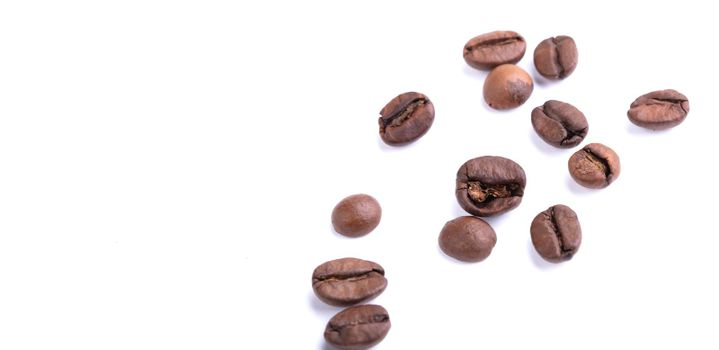 Scattered coffee beans on a white background. Arabica or robusta.