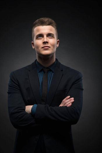 a portrait of a handsome young businessman is thinking and looking up against a black background. success concept
