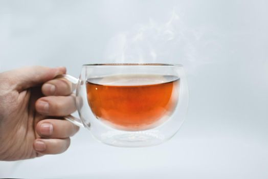 Man's hand holding a transparent cup with tea. Isolated on white background. Alpha