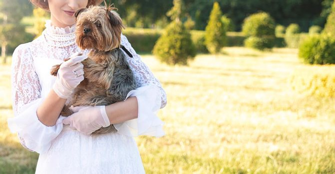 Retro portrait of a beautiful woman holding Yorkshire terrier