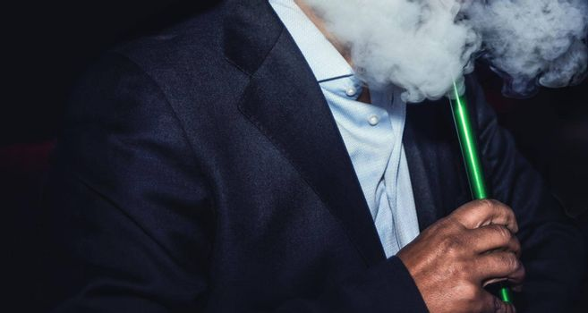 a man with no face smokes a hookah slowly exhaling smoke at the nightclub