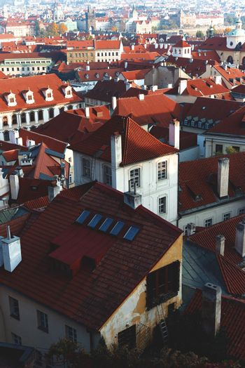 Top view to red roofs skyline of Prague city, Czech republic. Beautiful panoramic view of an famous historical city, during a vibrant winter sunrise.