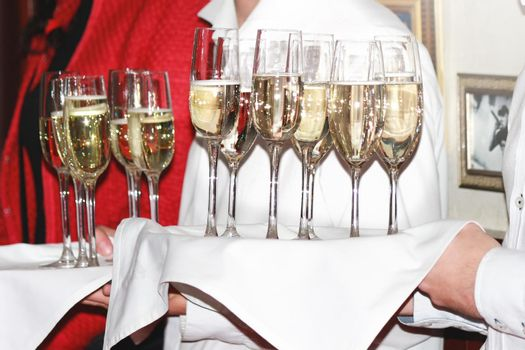 a waiter hands champagne glasses to guests at a corporate party. drinks