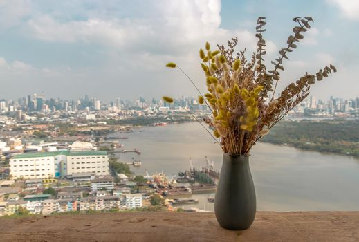 Dried flowers in ceramic vases handmade on a wooden desk on the balcony with city view background. Home decor. Space for text. Selective focus.