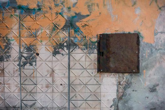 The wall of tiles is smeared with paint.
