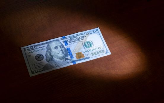 One hundred dollars was lying on the table and half lit by a ray of light.