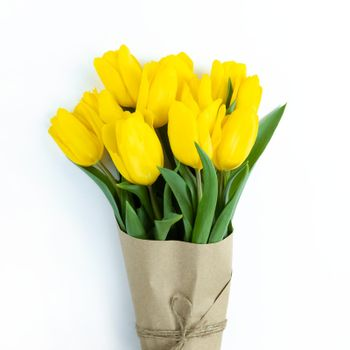 Bouquet of yellow tulips wrapped in craft paper on a white background.