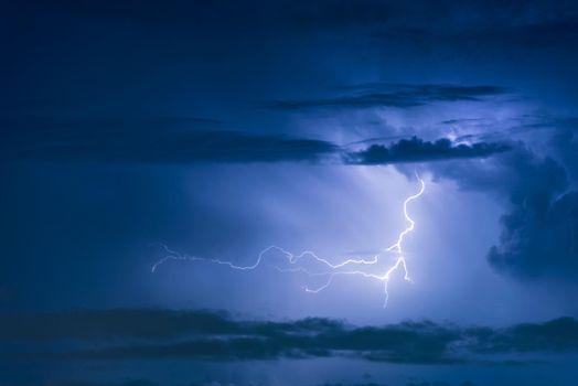 Thunder storm lightning strike on the dark cloudy sky background at night.