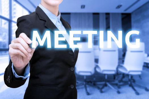 Business women writing Meeting word with blur meeting room and conference room in background.Photo for business corporation and teamwork concept