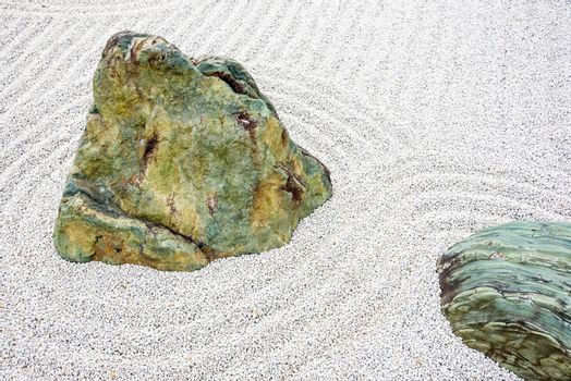 Japanese zen garden meditation stone in lines sand for relaxation balance and harmony spirituality or wellness in Kyoto,Japan.