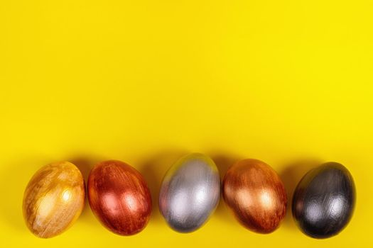 Easter. Multi-colored eggs on a uniform yellow background with place for text. View from above