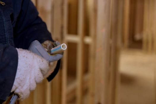Plumbing building contractor cut a polypropylene pipe with scissors the hands of a worker in white gloves