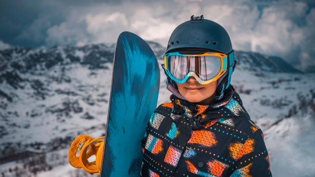 Closeup Portrait of Happy Active Girl Enjoying Beautiful Winter Ski Resort. Pretty Woman Wearing Protective Helmet and Mask, Holding Snowboard. Standing on the Top of Mountain.