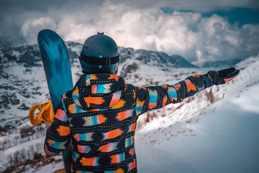 Rear View Of a Female Snowboarder Enjoying Amazing View of a Snowy Mountains with Raised Up Hand. Active Healthy Lifestyle. Spending Winter Holidays on Ski Resort.