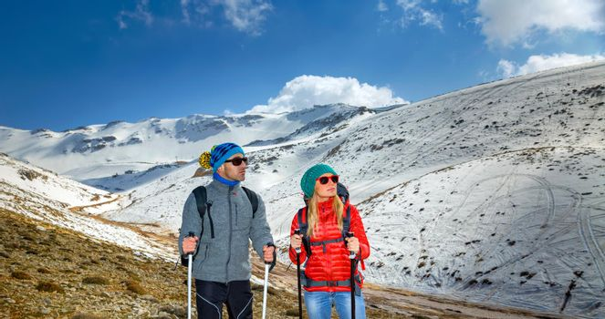 Nice Couple Climbing the Mountain with Trekking Poles. Enjoying Amazing View. Happy Active Winter Holidays. Zest for Life.