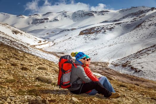 Happy Young Couple Sitting and Hugging in the Mountains at the Base Camp. Enjoying beautiful View on Snowy Mountains. Active Sportive Lifestyle. Winter Holidays Concept.