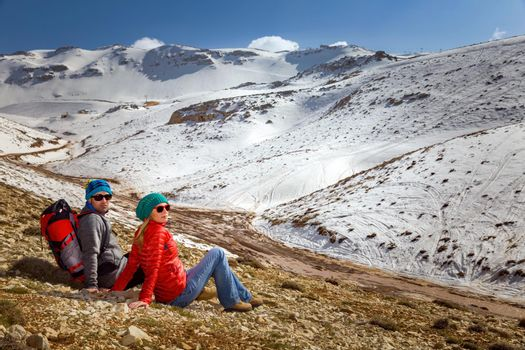 Happy Young Couple Sitting and Resting in the Mountains at the Base Camp. Enjoying Adventure Hike in the Beautiful Snowy Mountains. Active Sportive Lifestyle. Winter Holidays Concept.