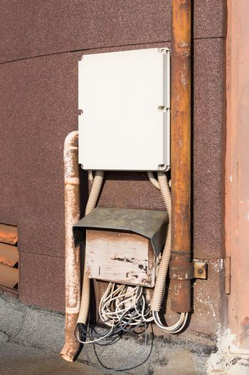 Old electrical cabinet and wires on wall.