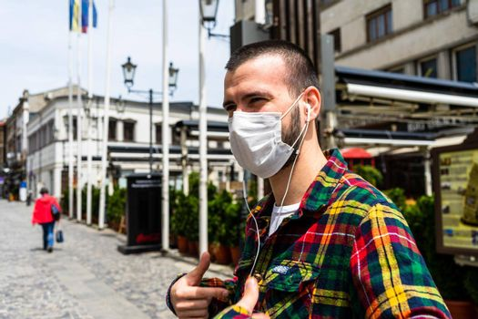 Funky hipster young man wearing medical mask in Bucharest, Romania, 2020