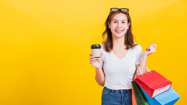 woman smiling hold shopping bags multi-color and take away coffee cup