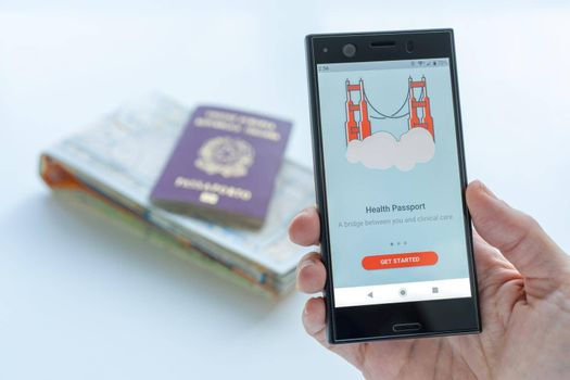 Milan, Italy - 01 26 2020: Digital Health Passport app for smartphone. background with a map and a passport. Coronavirus and traveling concept.
