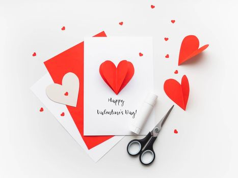 Valentine's Day greeting card. DIY holiday card with red paper volumetric heart, symbol of love and romance. Handmade card made with scissors, glue and colored paper.