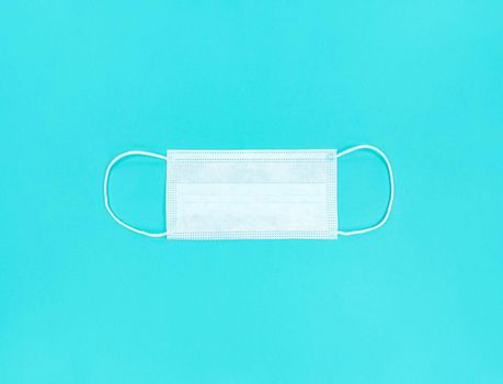 Medical disposable face mask on a blue background.