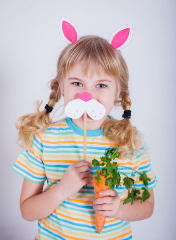 Cute little girl with bunny ears on gray background