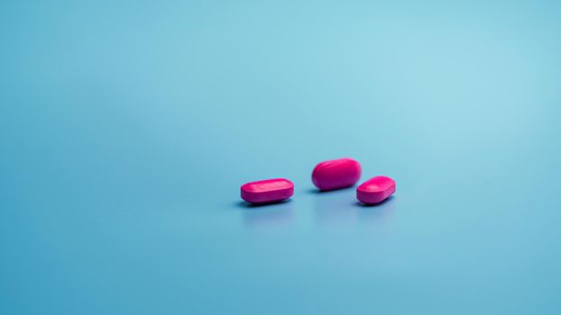Pink tablets on blue background. Painkiller medicine. Ibuprofen tablets pills. Pharmaceutical industry. Drug for treatment migraine headache. Community pharmacy product. Cancer pain management concept