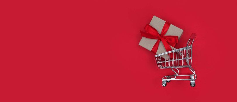Supermarket trolley and gift box on a red background with copy space. Shopping concept.