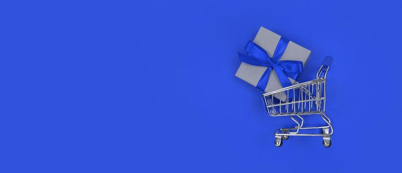 Supermarket trolley and gift box on a blue background with copy space. Shopping concept.