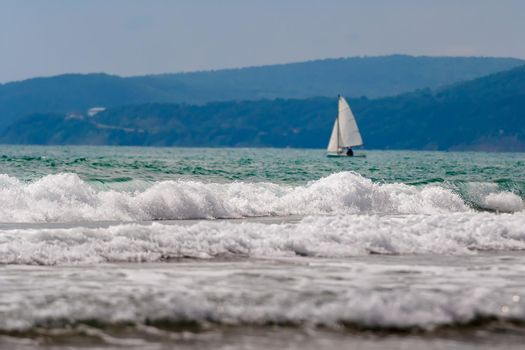 Seascape, a lone sailboat drifting on the waves.
