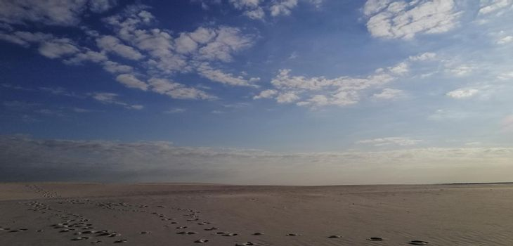 desert landscape. an artificial desert after the enrichment of sands by a metallurgical plant. Sand to the horizon. Blue sky and white clouds. Footprints in the sand.