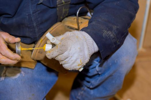 Man gluing parts cement glue off a piece of polypropylene pipes for installation water line