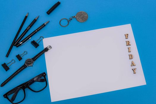 Stationery and blank sheet on a blue background. The inscription Friday on a sheet of wooden letters. Pens, watches, glasses, pencils. Flat lay. Copy space for inscription. Workplace. Nobody.