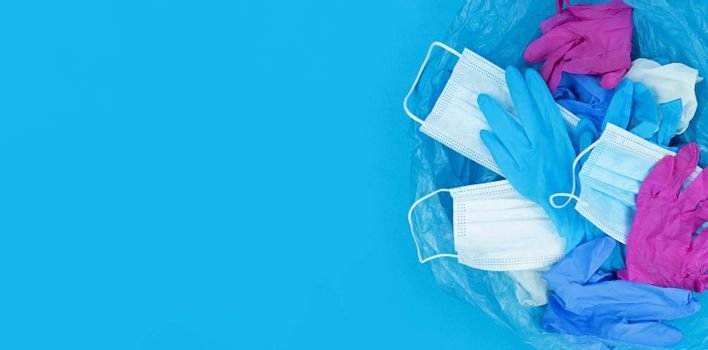 Medical pandemic coronavirus waste, face masks and latex gloves in garbage bag on a blue background with copy space.