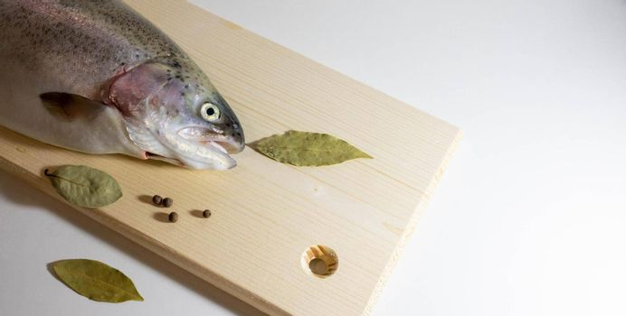 Half a trout fish with its mouth open lies on a wooden board on a white background.