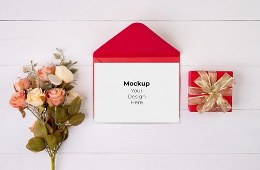 Valentine day, greeting card mockup and letter and flower on wooden table, postcard blank and gift box with romance on desk, present in anniversary and celebration, top view, holiday concept.