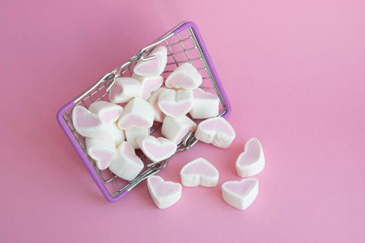 Valentine's Day, top view. Marshmallows pink hearts spilled out of a toy basket on a pink background, copying the space, the concept of love. The concept of buying love.