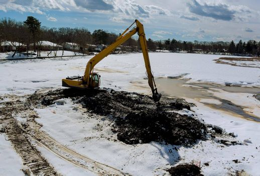 Cleaning the bottom of the lake with a excavators dredge on winter snow