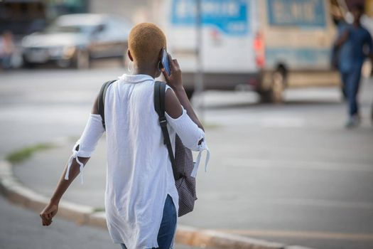 African American girl talking on a cell phone. African girl with a beautiful short fashionable hairstyle. Girl communicates using a smartphone. Foreign student. Migrant students.